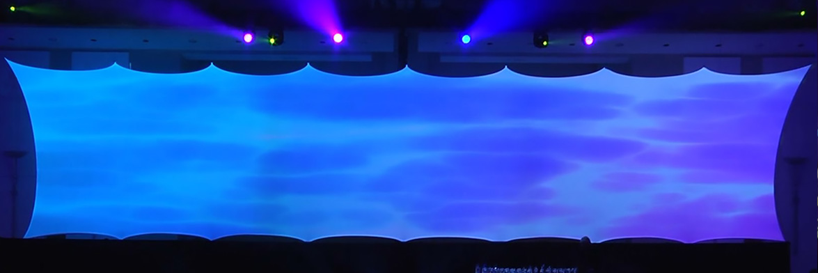 A massive stretch projection screen with 18 rigging points with blue light projected onto it.