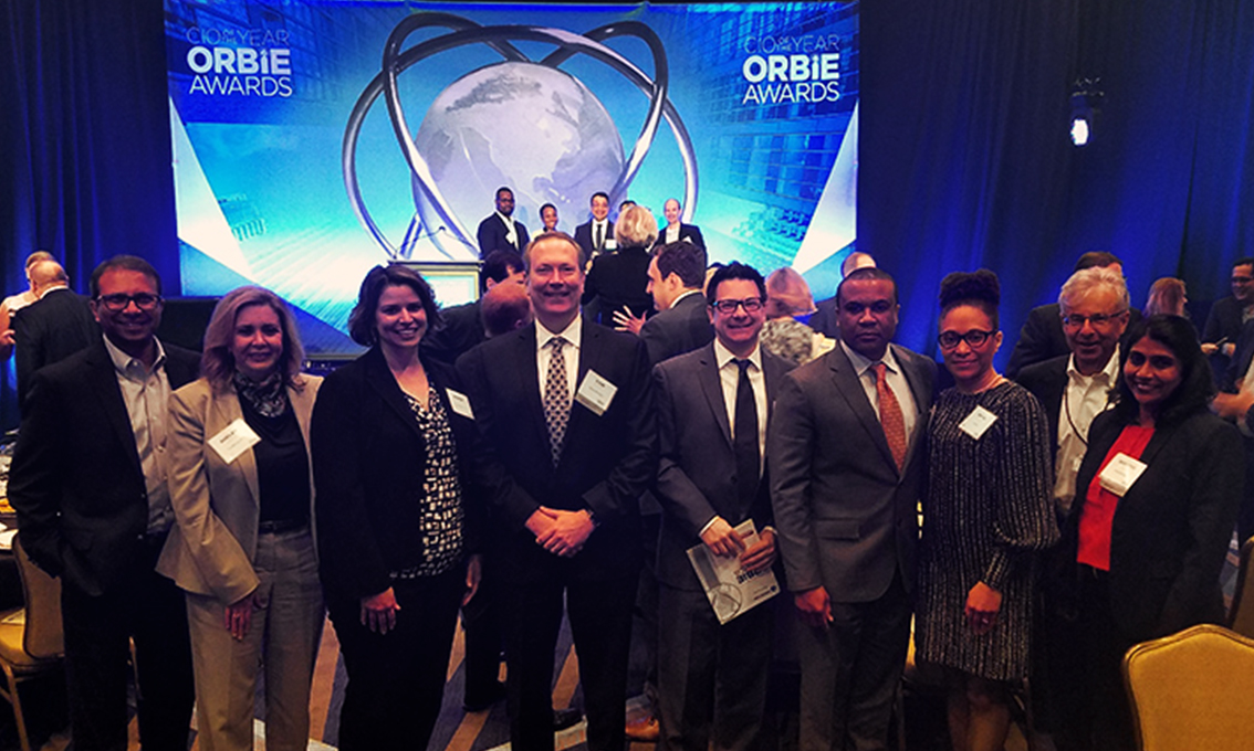A group of people stand in front of the printed Quick Wall for the Orbie Awards