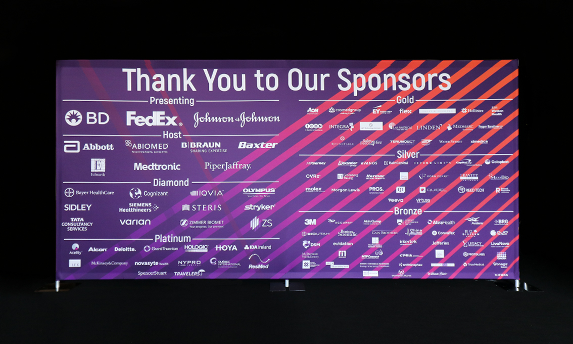 A large printed Quick Wall in shades of purple used as a sponsorship wall thanking various corporate sponsors